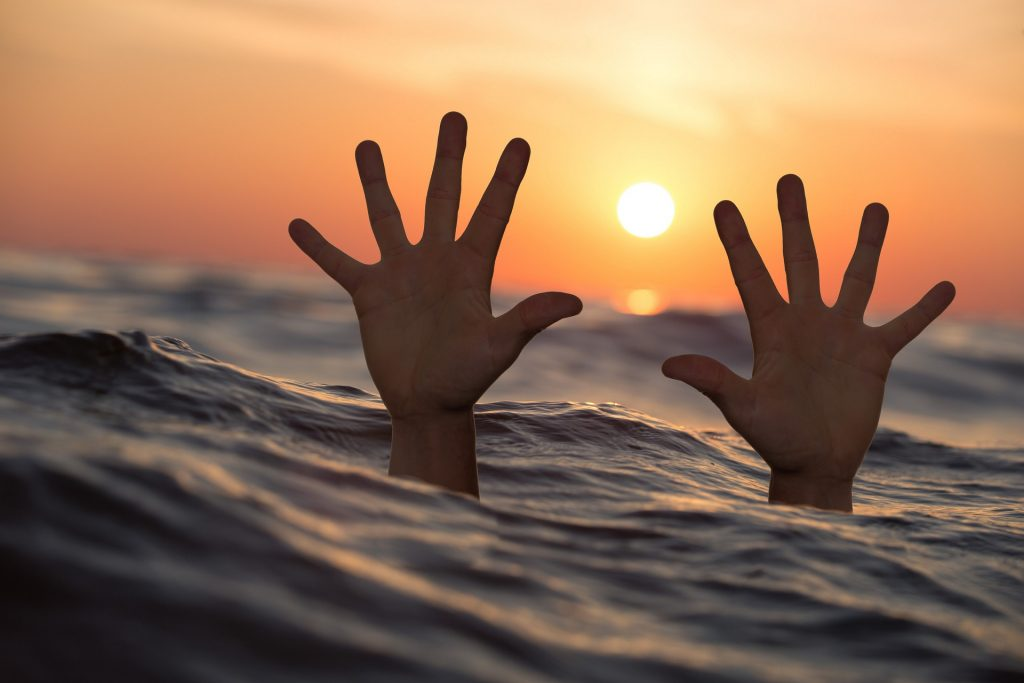 Two hands outstretched above the ocean, just above the surface and in front of the sun, low in the sky-
